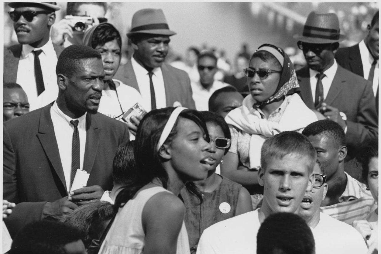 Black and white photo of a small group within a peaceful 1960s civil rights protest. The mostly black men are wearing dark suits, hats, and skinny ties. A young black woman in a sleeveless white dress looks in another direction. At front, a young white man looks intently at the camera.